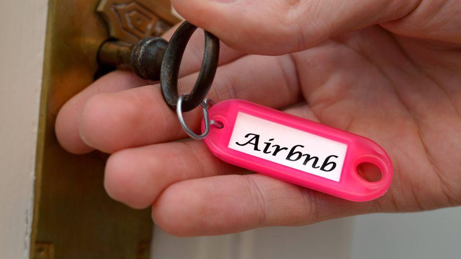 """Mann steckt Wohnungsschlüssel mit der Aufschrift """"Airbn"""" in ein Schloss."""