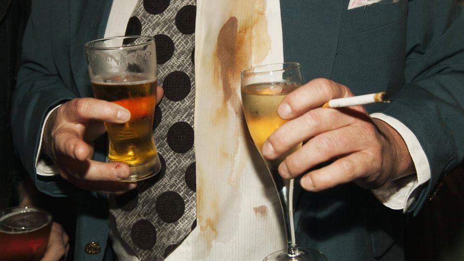 Ein Mann hält zwei Getränke und eine Zigarette in den Händen.
