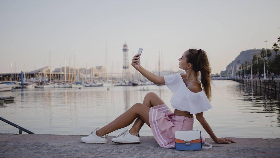 Junge Frau mit Smartphone am Hafen von Barcelona.