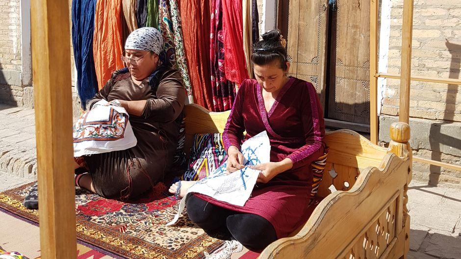 Die beiden Frauen, die gerade an Kissenhüllen arbeiten, gehören zu den 18 Stickerinnen, die in einer Textilwerkstatt in einer ehemaligen Medrese in Chiwa beschäftigt sind.