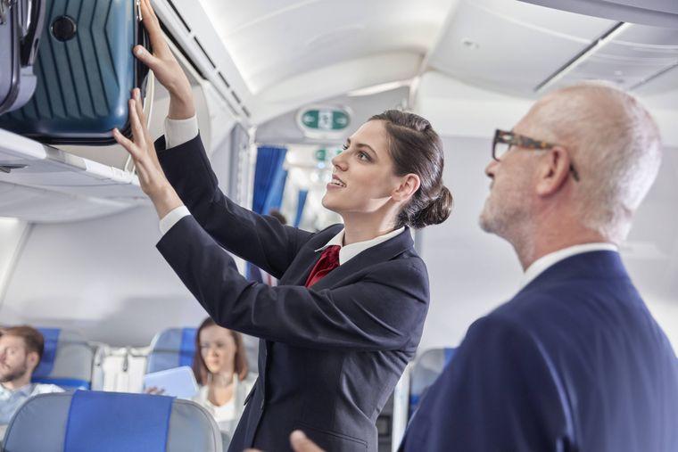 Eine Flugbegleiterin hilft einem Reisenden beim Verstauen des Handgepäcks.