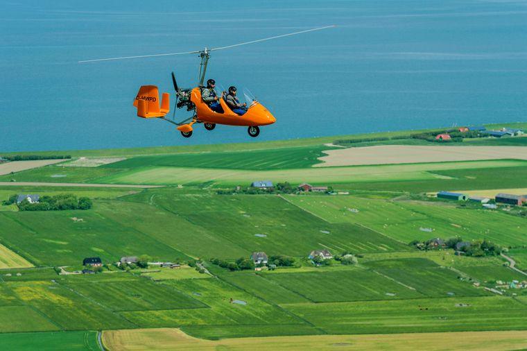 Tragschrauber im Flug über Pellworm und Nordfrieslands Küste.