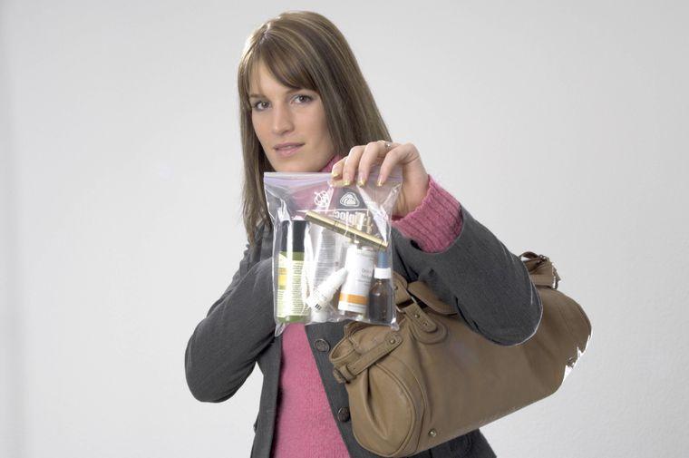 Junge Frau hält eine durchsichtige Plastiktüte mit verschieden Kosmetika.