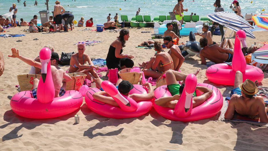 Feiernde Menschen in Flamingo-Schwimmreifen am Ballermann