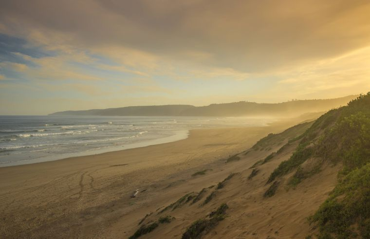 Sonnenuntergang an einem verlassenen Sandstrand am Westkap in Südafrika