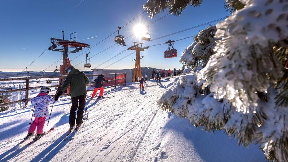 Skifahrer auf dem Fichtelberg in Oberwiesenthal – mit Blick auf die historische Schwebebahn.
