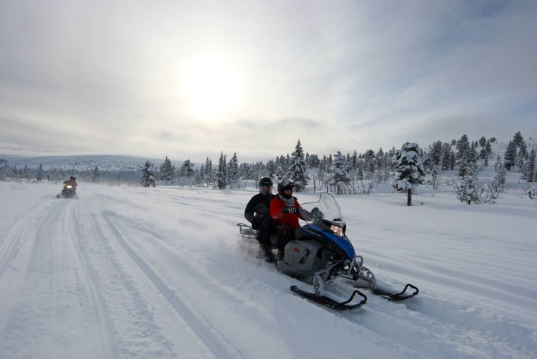 Touristen erkunden auf Schneemobilen die Umgebung.