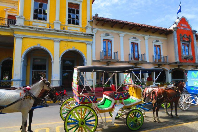 Kutschen in Granada vor den typischen Kolonialbauten.