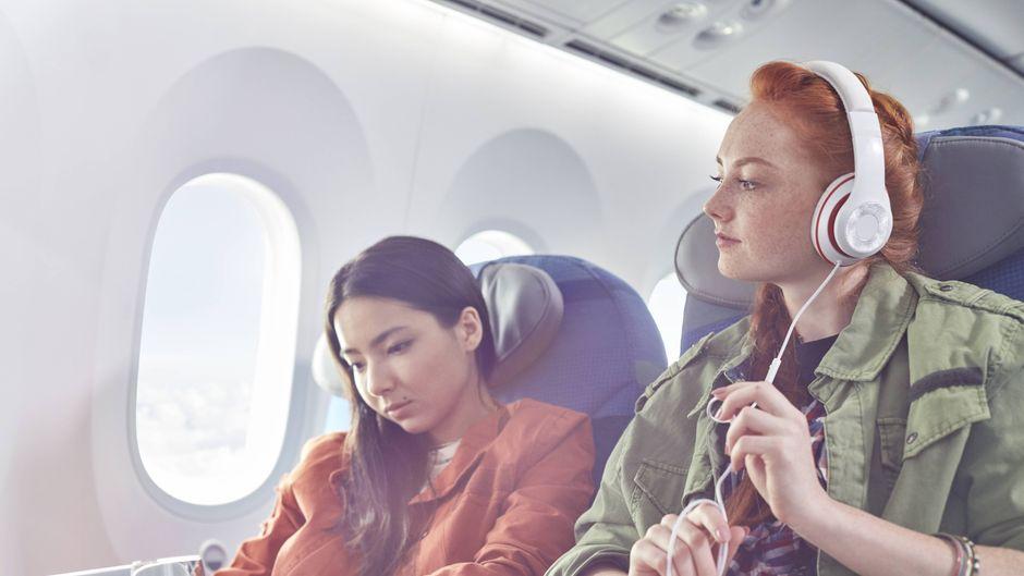 Zwei junge Frauen sitzen im Flugzeug auf benachbarten Sitzplätzen.
