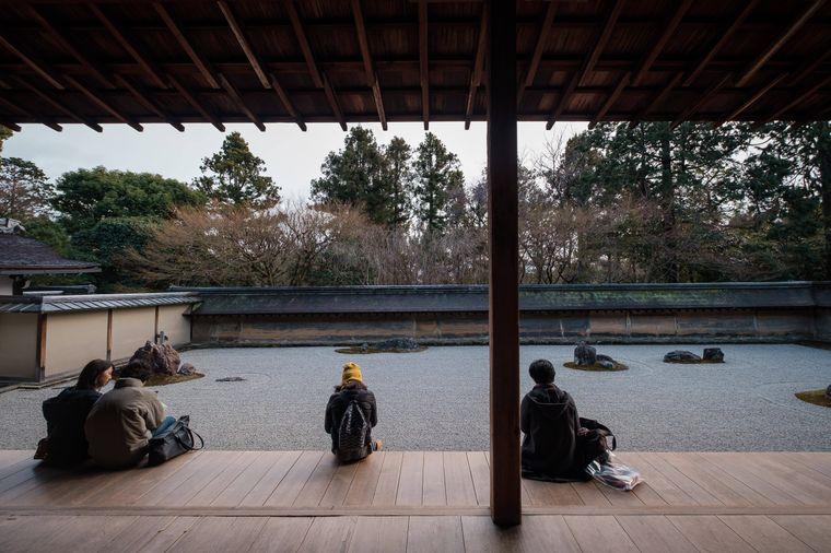 Touristen sitzen im Garten des Tempels Ryoan-ji, Kyoto, Japan.