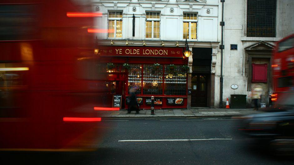 Ein roter Bus fährt vor einem Pub in London, England, vorbei.