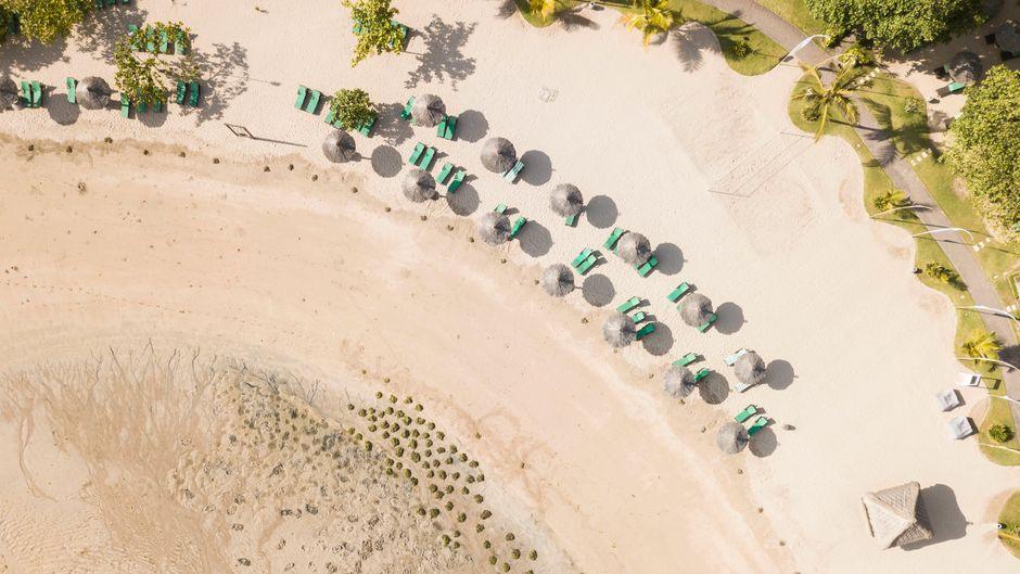 Blick auf einen Strand mit Sonnenstühlen und Sonnenliegen. Die Zeichen stehen auf Urlaub – auch dank der gelockerten Einreiseregeln in Deutschland.