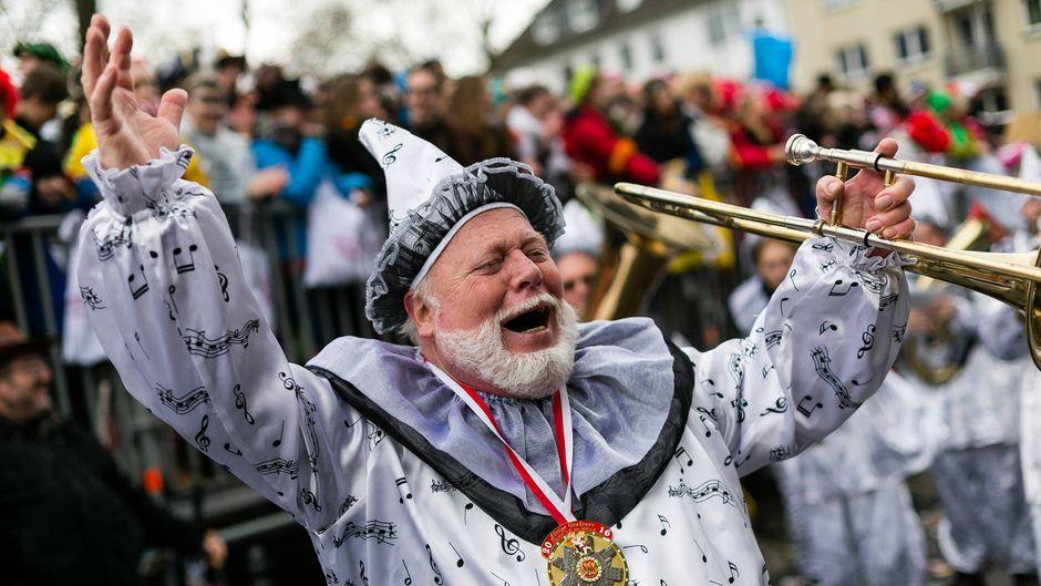 Ein Mann in einem Kostüm wirft während dem Rosenmontagszug vor Freude die Hände in die Luft.
