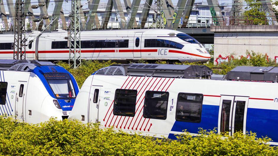 Ein ICE der Deutschen Bahn und ein Regionalzug warten auf den Schienen am Bahnhof Köln-Deutz.