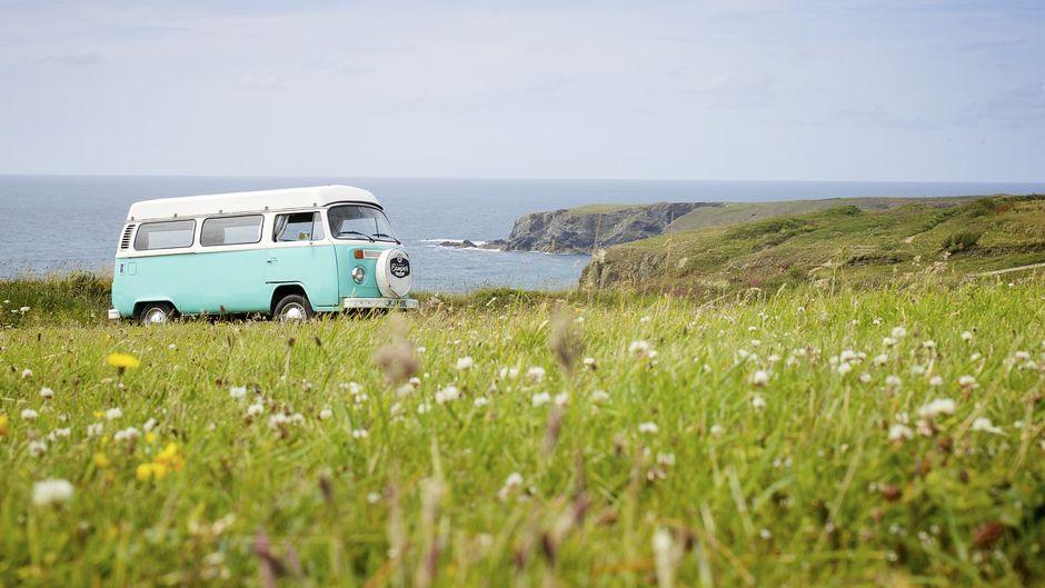 VW-Bus vor einer Küste.