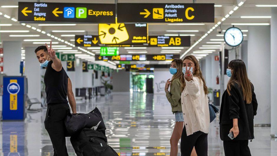 Urlauber mit Mundschutz bei der Ankunft am Flughafen Palma de Mallorca in Spanien.