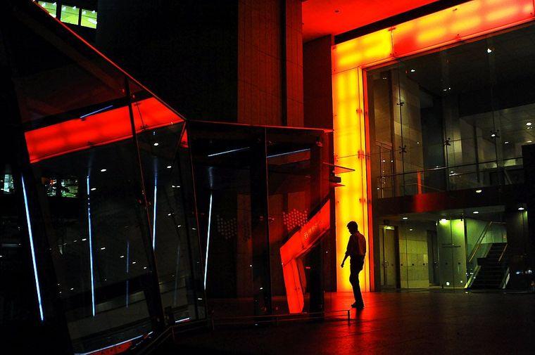 Ein einsamer Fußgänger vor orange beleuchteter Fassade.