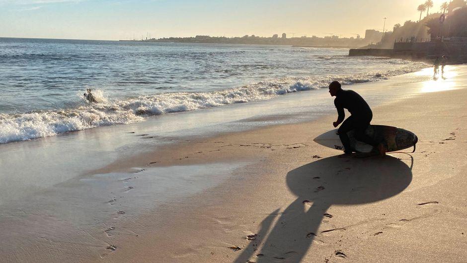 Ein Surfer an Portugals Strand Praio de Tamariz in der Abendsonne. Können wir schon sorglos Urlaub für 2021 buchen?