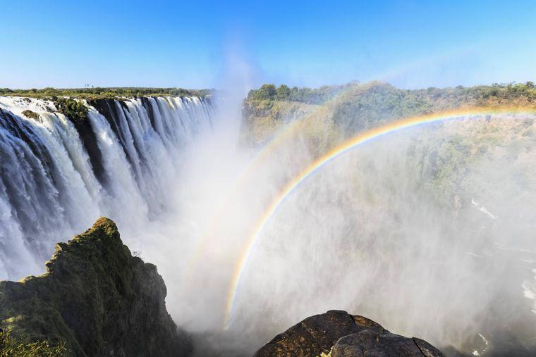 Die Victoriafälle in Zimbabwe sind für sich genommen schon ein Hingucker. Ein Regenbogen macht das Urlaubs-Foto aber perfekt.