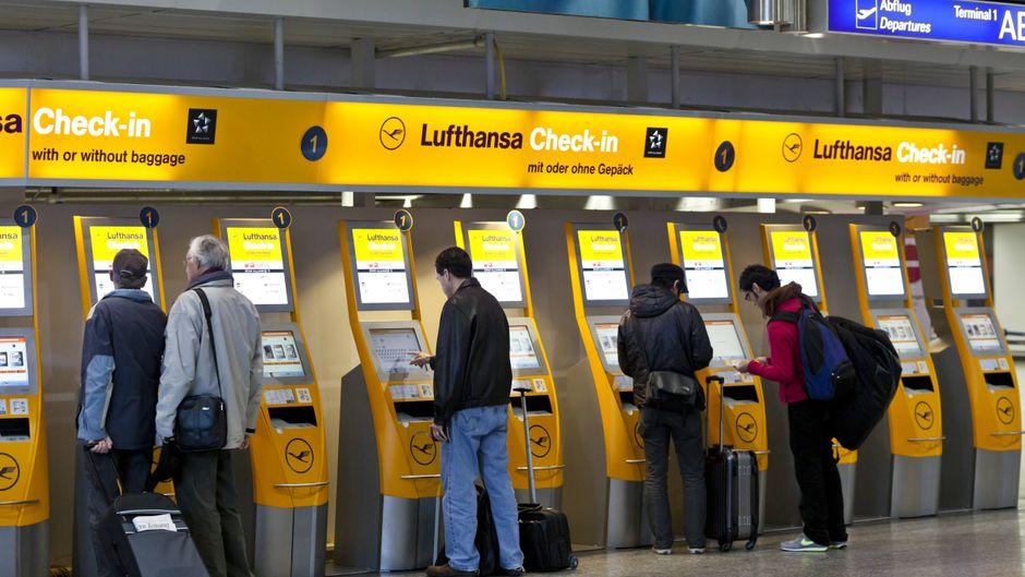 Passagiere checken an den Lufthansa-Schaltern ein.