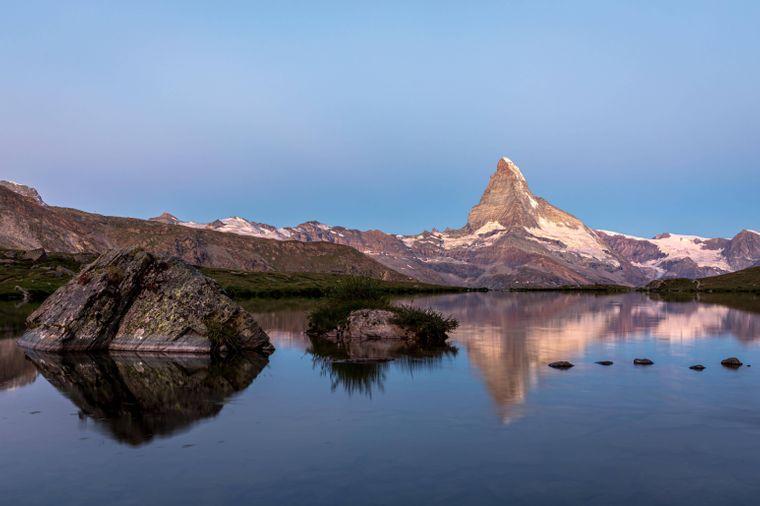 Matterhorn bei Sonnenaufgang, reflektiert im Stellisee: Lass die Naturkulisse auf dich wirken.