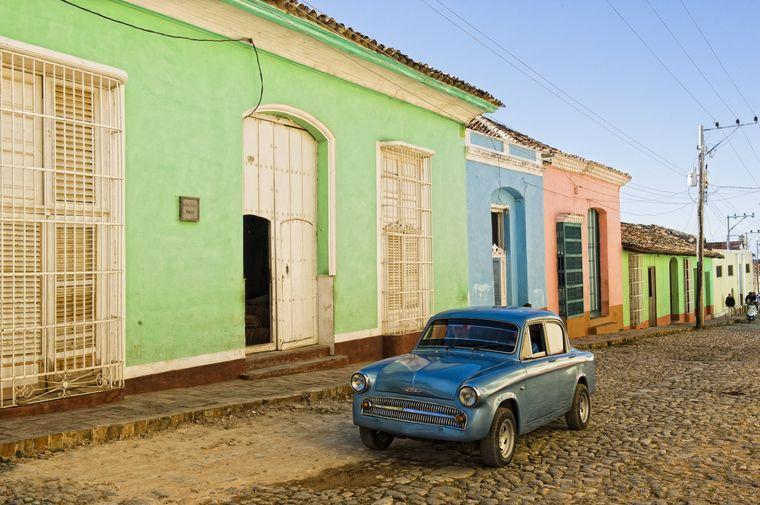Oldtimer vor bunten Kolonialhäusern in Trinidad in Kuba.