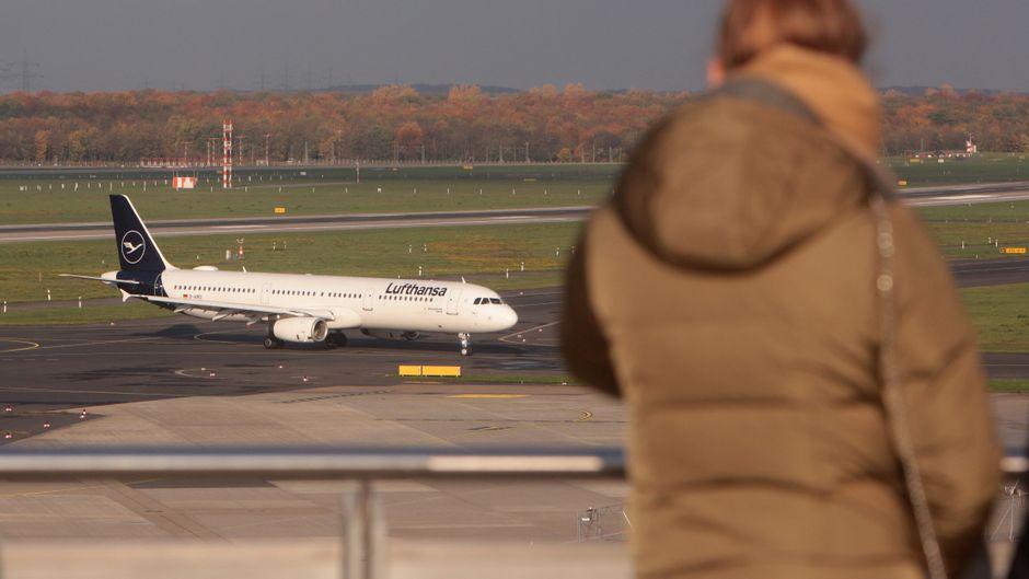 Eine Frau steht an der Reling und schaut auf ein Flugzeug.