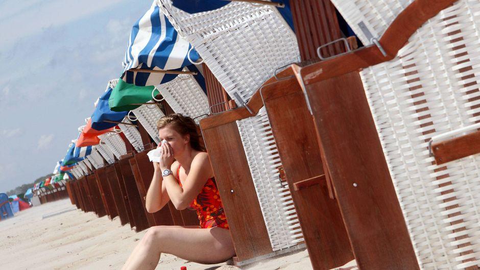 Eine Frau sitzt am Strand und putzt sich die Nase.