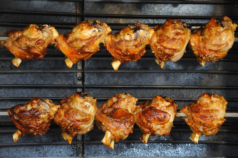 Schweinshaxen hängen aufgespießt im Grill – dort werden sie knusprig braun.