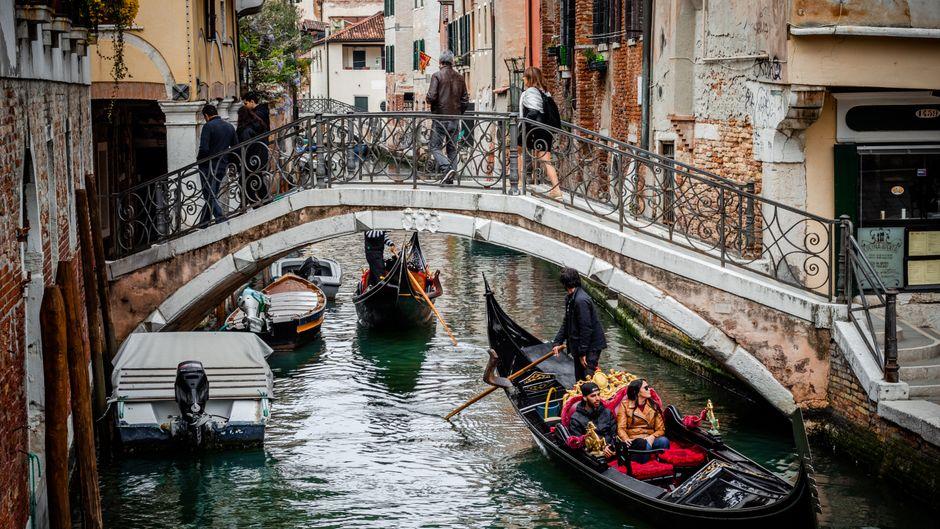 Gondeln fahren durch Venedigs Kanäle.