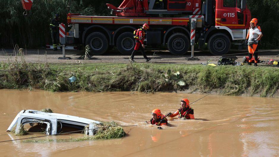 Rettungskräfte bergen das Auto einer Frau auf Sardinien, Italien, nach heftigem Unwetter.