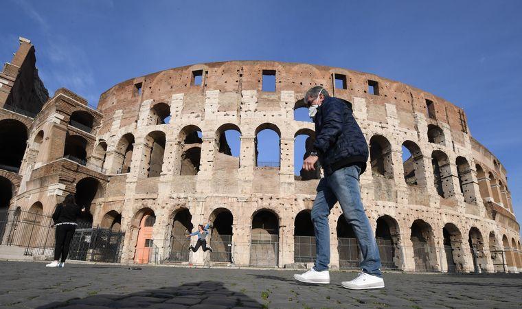Mann mit Gesichtsmaske vor dem Kolloseum in Rom, Italien.