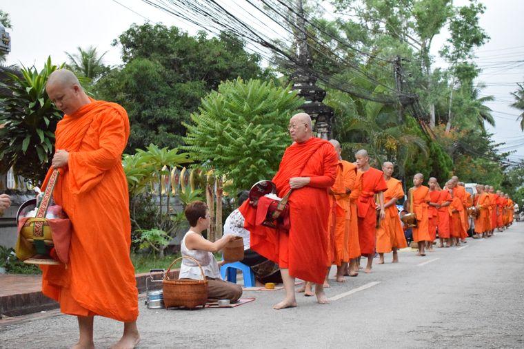 Beim Opfergang der Mönche am Morgen in Luang Prabang ist es nicht erlaubt, die Männer anzuschauen, während man ihnen ein Gabe in die Körbe legt.