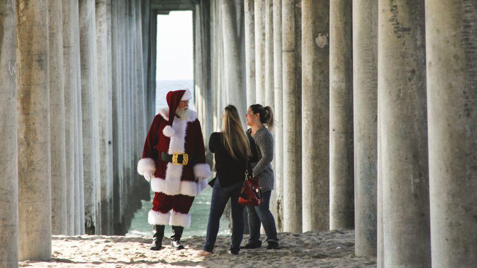Ein Weihnachtsmann und zwei Frauen unter einer Brücke.