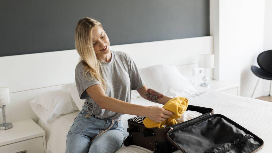 Frau sitzt auf einem Bett und packt ihren Koffer. (Symbolfoto)