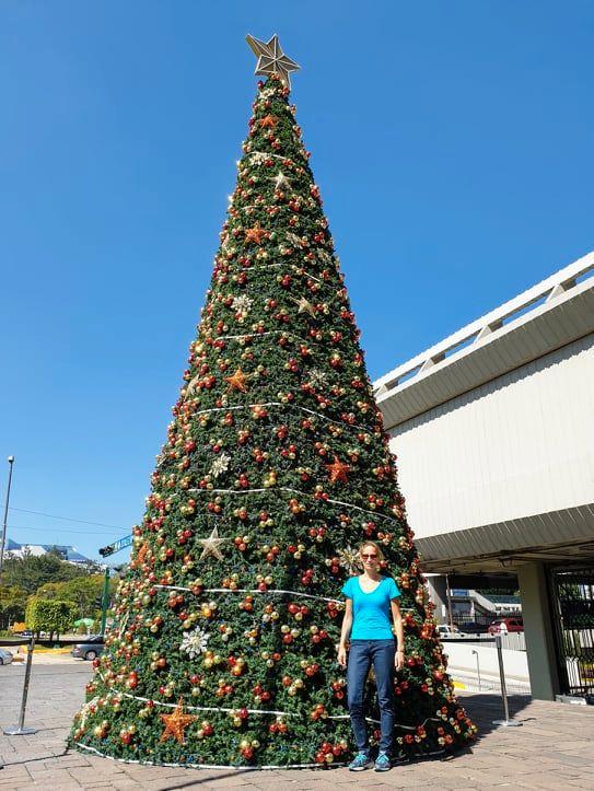 Weltreisende Sonja Schneider steht vor einem riesigen Weihnachtsbaum in Guatemala.