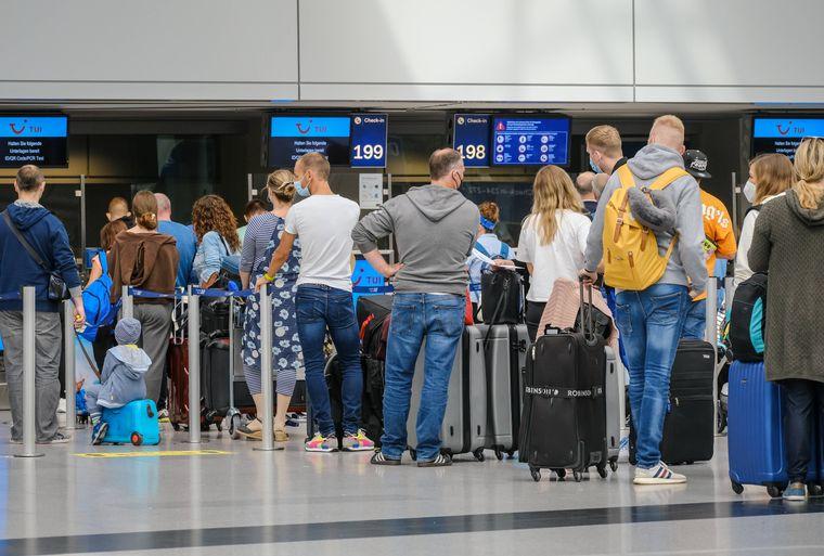 Ferienstart in NRW: Urlauberinnen und Urlauber stehen mit Koffern in einer Menschenschlange am Check-in-Schalter am Flughafen Düsseldorf.