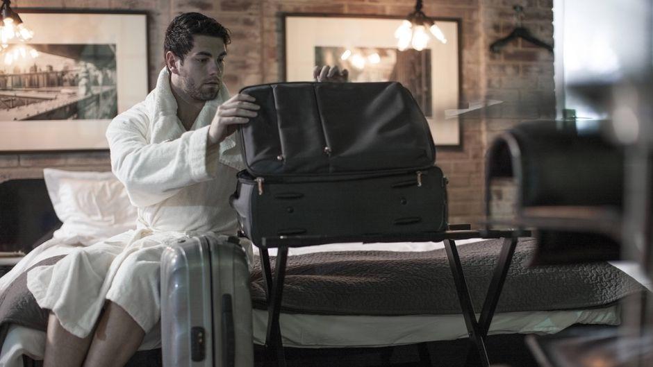 Mann packt seinen Koffer im Hotelzimmer
