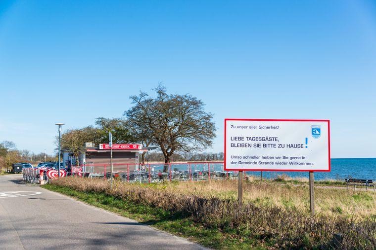 """""""Liebe Tagesgäste, bitte bleiben Sie zu Hause"""" – Hinweisschild an der Kieler Bucht."""