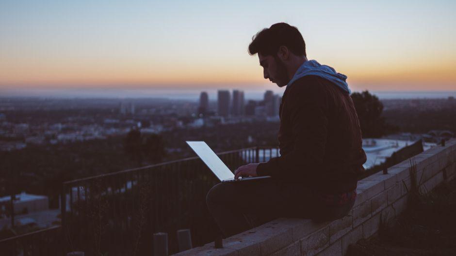 Mann sitzt mit seinem Laptop auf einer Aussichtsplattform bei Sonnenuntergang.