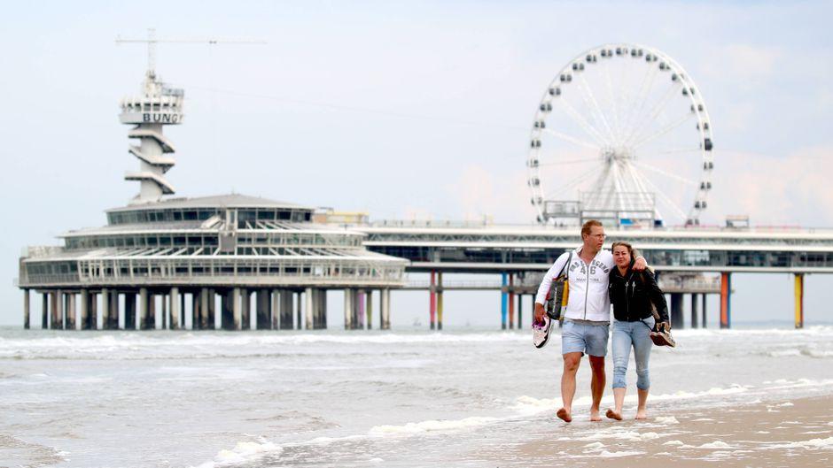 Ein Paar spaziert am Strand von Scheveningen. Der Ort wird wie die ganzen Niederlanden zum Hochinzidenzgebiet.