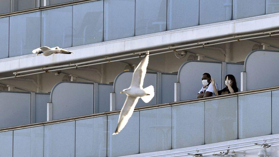 """Passagiere mit Mundschutz auf ihrem Balkon auf dem Kreuzfahrtschiff """"Diamond Princess"""", das sich unter Quarantäne befindet."""