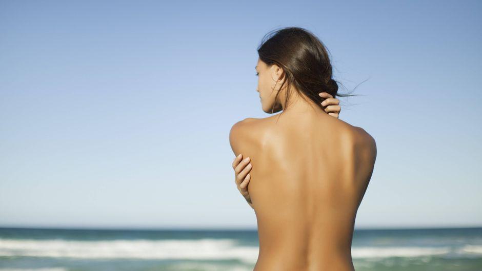 Eine Frau steht oben ohne am Strand.