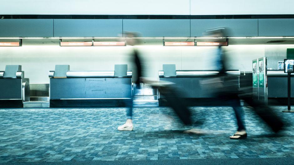 Gehetzte Menschen mit Koffer am Flughafen.