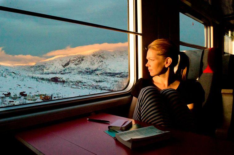 Ein Frau sitzt in einem Nachtzug und schaut aus dem Fenster auf die schwedische Landschaft bei Abisko.