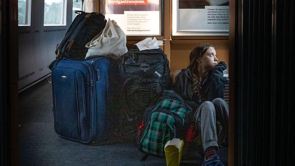 Greta Thunberg mit ihrem Reisegepäck im Gang eines IC der Deutschen Bahn.