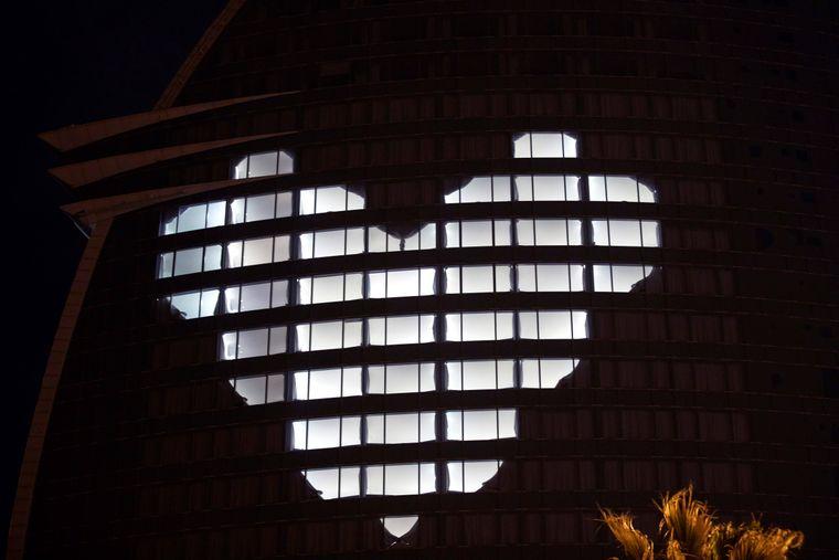 Ein großes Herz erstrahlt auf den Hotelfassaden in Barcelona, Spanien.
