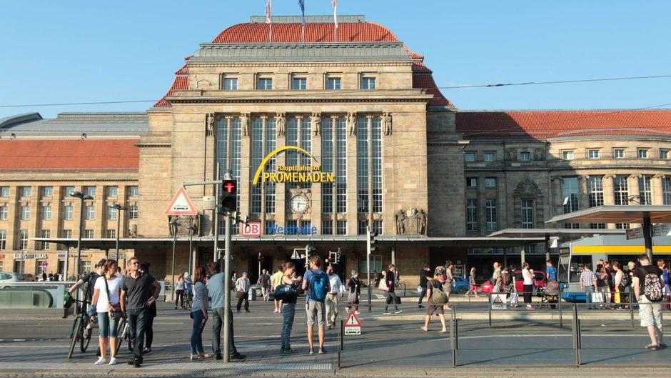 Fahrgäste und Passanten stehen an einer Ampel vor dem sanierten Leipziger Hauptbahnhof.