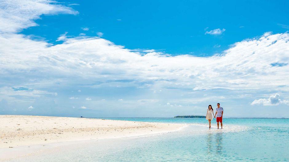Ein Paar läuft an einem Strand auf den Malediven. Sonne und Wärme genießen im November geht auf den Inseln sehr gut.