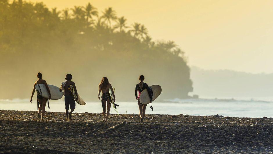 Surfer gehen im Morgenlicht am Strand von Bali Richtung Meer.